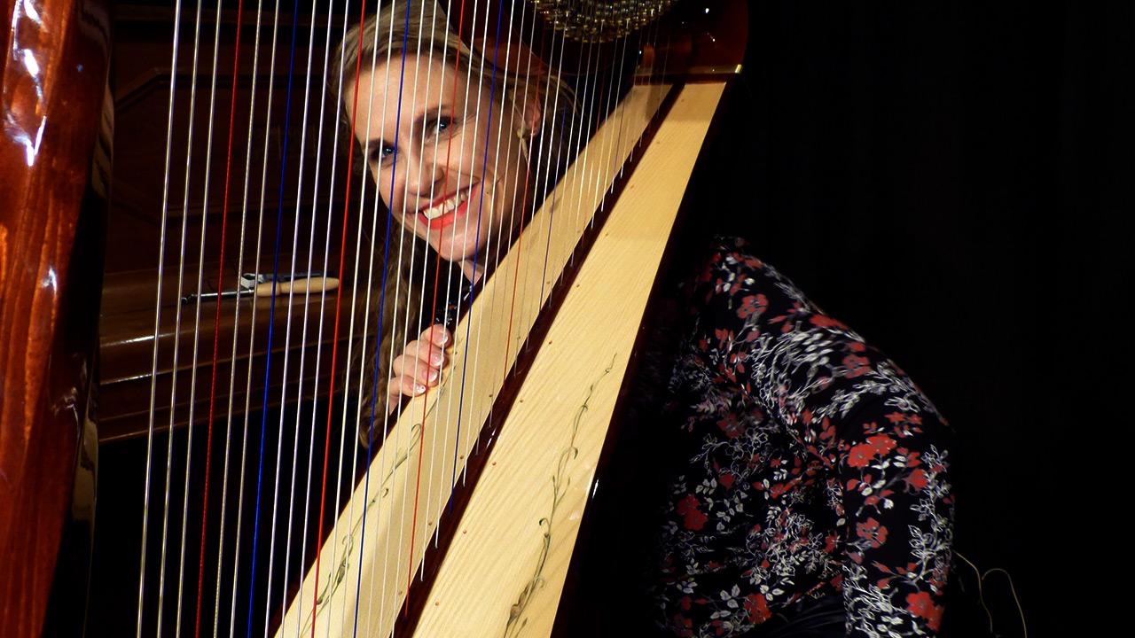Geli schaut hinter der Harfe hervor